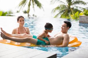 Happy young Chinese family having fun in swimming poolの写真素材 [FYI02230923]