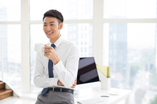 Cheerful young Chinese businessman taking a coffee breakの写真素材 [FYI02230955]