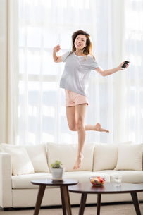 Cheerful young Chinese woman jumping and listening to music on sofaの写真素材 [FYI02230958]