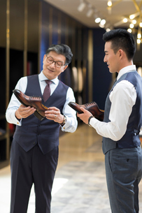 Chinese businessman choosing leather shoesの写真素材 [FYI02230960]