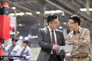 Businessman and engineer talking in the factoryの写真素材 [FYI02230980]