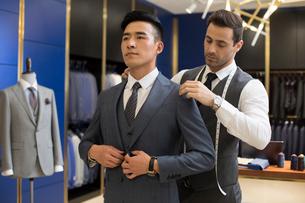Chinese fashion designer examining suit on customerの写真素材 [FYI02231002]