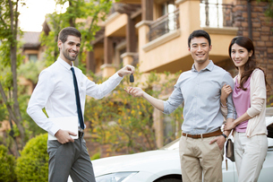 Happy young Chinese couple receiving car key from car salespersonの写真素材 [FYI02231014]