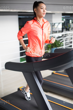 Young woman running on treadmill in gymの写真素材 [FYI02231021]