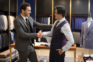 Confident Chinese fashion designer shaking hands with businessmanの写真素材 [FYI02231024]