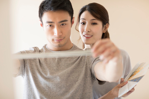 Young Chinese couple working on home renovationの写真素材 [FYI02231065]