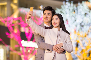 Cheerful young Chinese couple taking self portrait with smart phoneの写真素材 [FYI02231072]