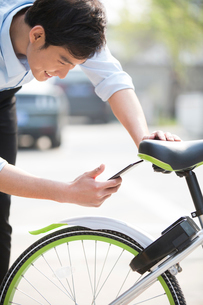 Young man scanning a QR code to unlock a share bikeの写真素材 [FYI02231093]
