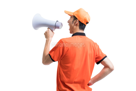 Cheerful Chinese pizza delivery person shouting through megaphoneの写真素材 [FYI02231112]
