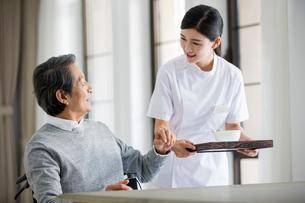 Nursing assistant taking care of senior man in wheel chairの写真素材 [FYI02231115]