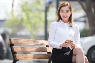 Cheerful young Chinese businesswoman drinking coffeeの写真素材 [FYI02231116]