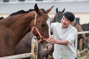 Cheerful young Chinese man and horseの写真素材 [FYI02231117]