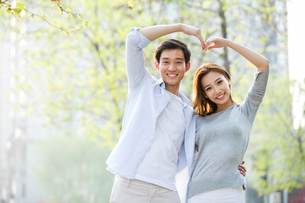 Happy young Chinese couple doing heart shape gestureの写真素材 [FYI02231120]