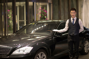 Chinese chauffeur standing next to the carの写真素材 [FYI02231153]