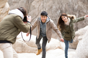 Happy young Chinese friends taking pictures outdoors in winterの写真素材 [FYI02231154]