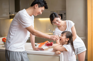 Young father feeding daughter fruit in the kitchenの写真素材 [FYI02231171]