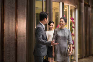 Confident Chinese business people talking in hotel lobbyの写真素材 [FYI02231201]