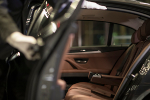 Chinese chauffeur opening car door for passengerの写真素材 [FYI02231219]