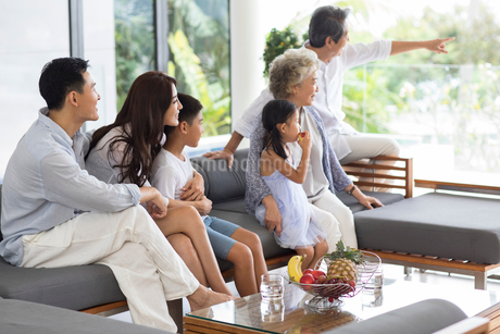 Happy Chinese family sitting on the sofaの写真素材 [FYI02231254]