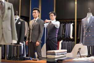 Chinese fashion designer taking measurement of customerの写真素材 [FYI02231271]