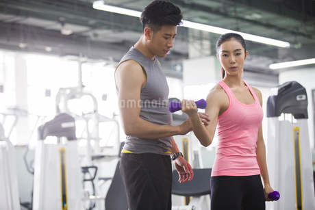 Young woman working with trainer at gymの写真素材 [FYI02231297]