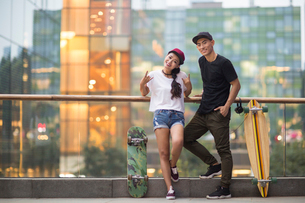 Cheerful young Chinese couple with skateboard datingの写真素材 [FYI02231303]