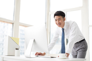 Cheerful young Chinese businessman working in officeの写真素材 [FYI02231311]