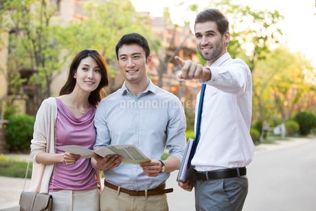 Happy young Chinese couple talking with confident businessmanの写真素材 [FYI02231317]