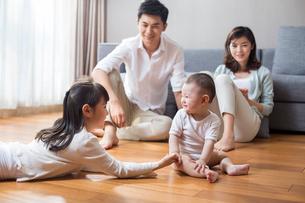 Happy young family lying on wooden floorの写真素材 [FYI02231336]