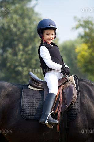 Cheerful little Chinese girl riding horseの写真素材 [FYI02231345]