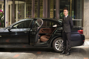Chinese chauffeur opening car door for passengerの写真素材 [FYI02231346]