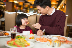 Cheerful Chinese father and daughter having buffet dinnerの写真素材 [FYI02231387]