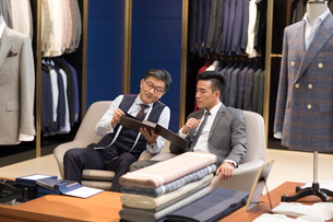 Chinese fashion designer and customer talking in menswear shopの写真素材 [FYI02231389]