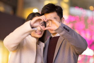 Cheerful young Chinese couple making heart shape with their handsの写真素材 [FYI02231394]