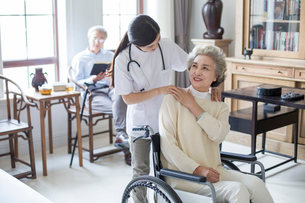 Nursing assistant taking care of senior woman in wheel chairの写真素材 [FYI02231402]