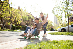 Happy young Chinese family playing with skateboardの写真素材 [FYI02231408]