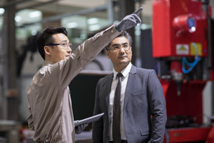 Businessman and engineer talking in the factoryの写真素材 [FYI02231412]