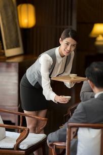 Elegance Chinese waitress holding two cups of teaの写真素材 [FYI02231439]