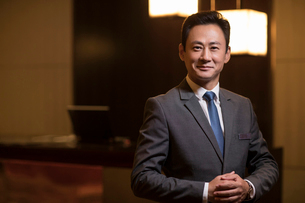 Portrait of confident Chinese hotel managerの写真素材 [FYI02231440]