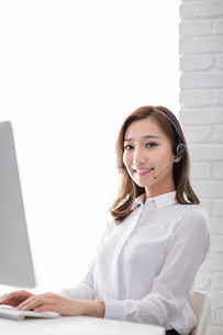 Cheerful young Chinese businesswoman with headset in officeの写真素材 [FYI02231480]