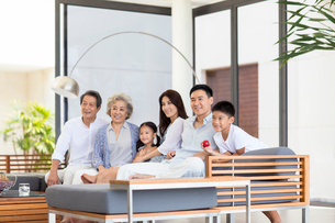 Happy Chinese family sitting on the sofaの写真素材 [FYI02231484]