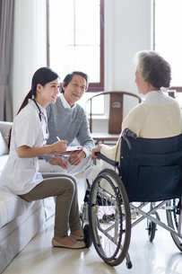 Nursing assistant taking care of senior woman in wheel chairの写真素材 [FYI02231495]