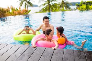 Happy young Chinese family having fun in swimming poolの写真素材 [FYI02231503]