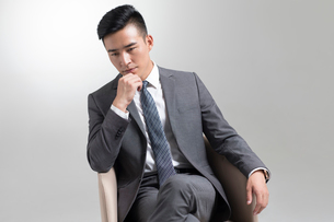 Confident young Chinese businessman thinkingの写真素材 [FYI02231511]