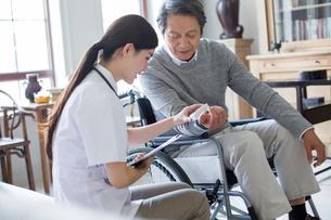 Nursing assistant taking care of senior man in wheel chairの写真素材 [FYI02231522]