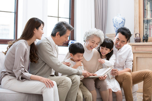 Happy Chinese family looking at photo album on sofaの写真素材 [FYI02231531]