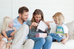 A surprised and happy mother opens her present as the family watchの写真素材 [FYI02231532]
