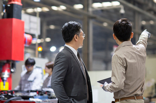 Businessman and engineer talking in the factoryの写真素材 [FYI02231540]