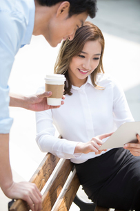 Young Chinese business people using digital tablet outdoorsの写真素材 [FYI02231557]
