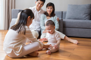 Happy young family sitting on wooden floorの写真素材 [FYI02231561]